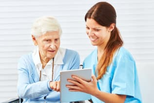senior woman and caregiver looking at the tablet