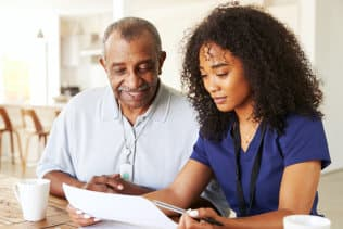 senior man and caregiver looking at the paper